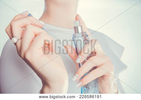 Woman In Red Dress Applying Perfume On Her Wrist