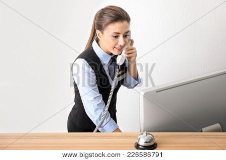 Female receptionist talking on phone in hotel