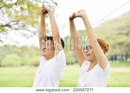 Happy Asian Couple In White Shirt Workout At The Park. Couple Are Smiling And Warming Up And Stretch