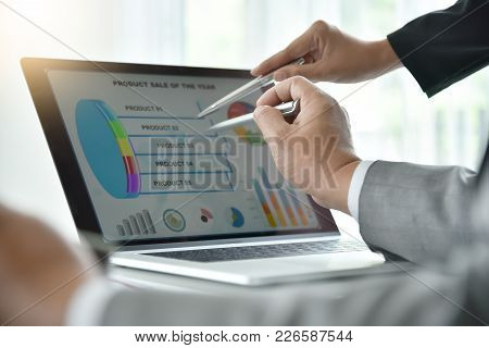 Businesswoman And Businessman Hands Is Pointing To Business Chart Or Graph On Laptop Screen With Pen