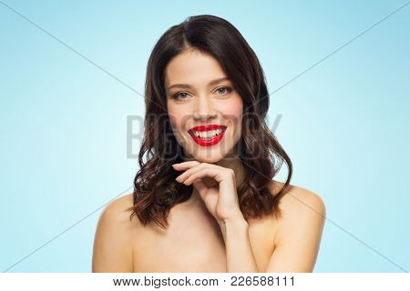beauty, make up and people concept - happy smiling young woman with red lipstick posing over blue background