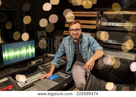 music, technology, people and equipment concept - man at mixing console in sound recording studio over festive lights