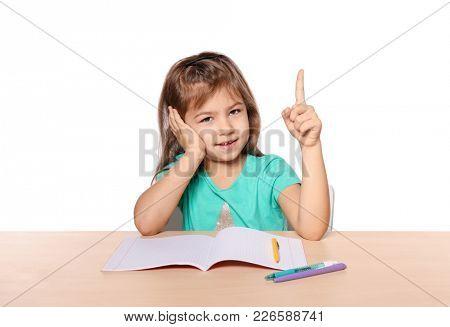 Cute little girl with raised index finger  against white background. Child doing her homework
