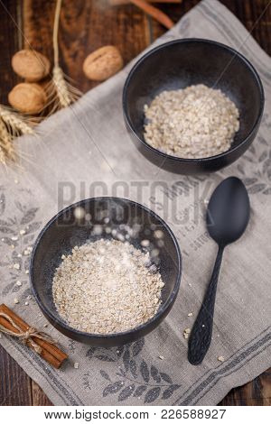 Easy And Healthy Breakfast. Leavening In A Bowl Of Dry Cereal Oatmeal. Still-life On A Wooden Backgr