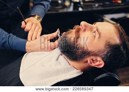 Close Up Image Of Barber Makes Beard Cut Of A Man.