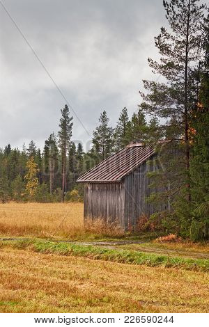 An Old Barn House Stands By The Small Road Leading To The Fields In The Rural Finland. The Autumn Co