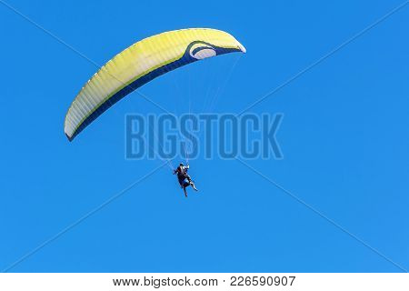 On The Background Of Blue Sky Soars A Glider Yellow-blue Colors
