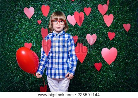 Ð¡ute child boy holding heart shaped balloon, surrounded by hearts over lawny background. First love. Valentine's Day.