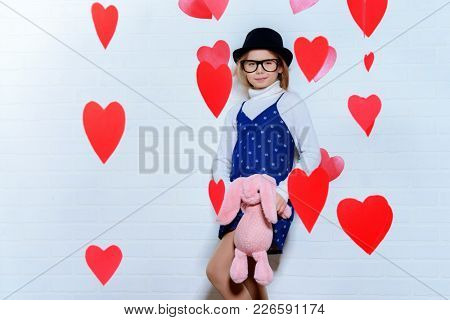 Valentine's Day concept. Happy pre-teen girl with plush rabbit in hands poses surrounded by little hearts. First love.