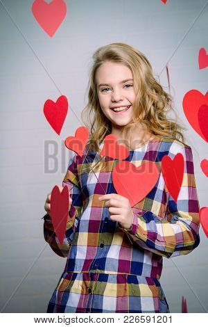 Valentine's Day concept. Happy pre-teen girl poses surrounded by little hearts. First love.
