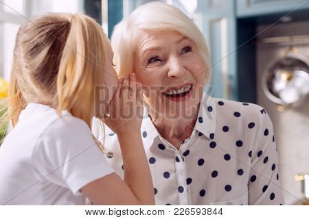 I Trust You. The Close Up Of A Charming Little Girl Telling Her Grandmother A Secret And Whispering
