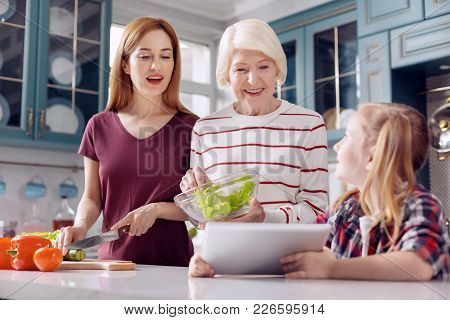 Important Help. Sweet Little Girl Showing A Recipe On The Tablet To Her Mother And Grandmother While