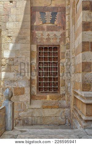 Grunge Wooden Aged Window With Iron Bars On Exterior Stone Bricks Wall Of Amir Aqsunqur Mosque (blue