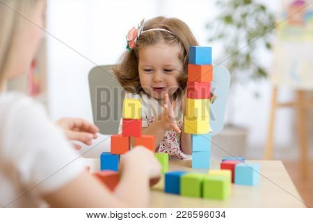 Mother And Child Playing Colorful Block Toys At Home Or Daycare