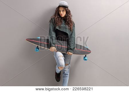 Teenage girl with a longboarding leaning against a gray wall