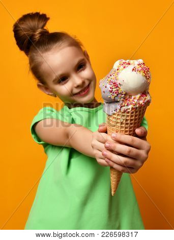 Pretty Baby Girl Kid Eating Licking Banana And Chocolate Ice Cream In Waffles Cone On Yellow Backgro