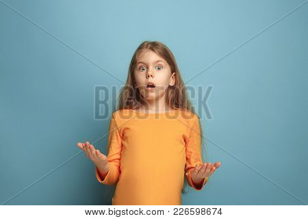 The Surprise, Delight. The Surprised Teen Girl On A Blue Studio Background. Facial Expressions And P