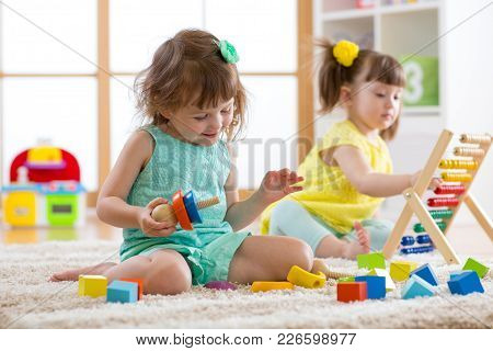 Kids Girls Are Engaging In Daycare. Two Toddler Children Playing With Educational Toys In Kindergart