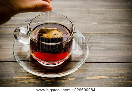 Hand Holding Tea Bag And Making Hot Tea