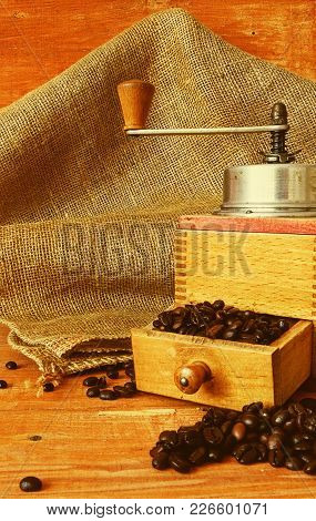 Vintage Coffee Mill And Coffee Beans On Wooden Background.