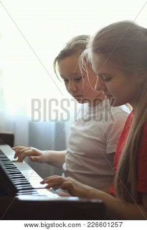 Two Teenagers Sisters Girl 14-years Old Plays The Piano At Home, Vertical Shot, Close Up
