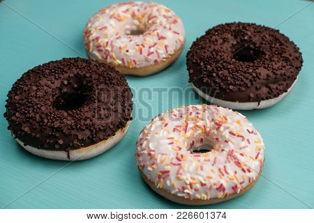 Four Donuts, Chocolate And White On A Turquoise Wooden Background. Side View. Closeup