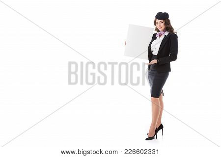 Attractive Stewardess Holding Empty Board And Looking At Camera Isolated On White