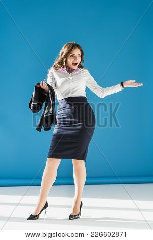 Attractive Happy Stewardess With Open Arms On Blue