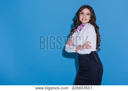 Attractive Smiling Stewardess With Crossed Arms On Blue