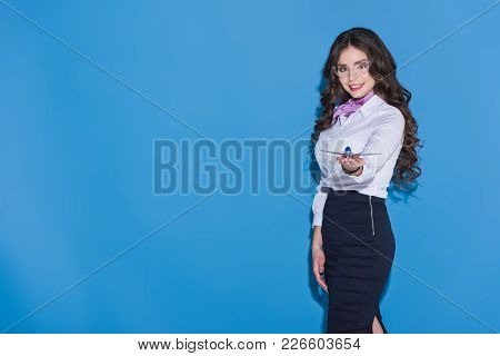 Attractive Stewardess Showing Plane Model In Hand On Blue