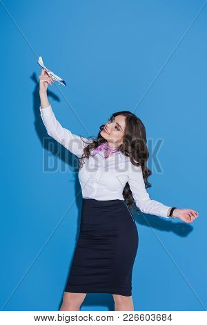 Attractive Stewardess Playing With Plane Toy On Blue