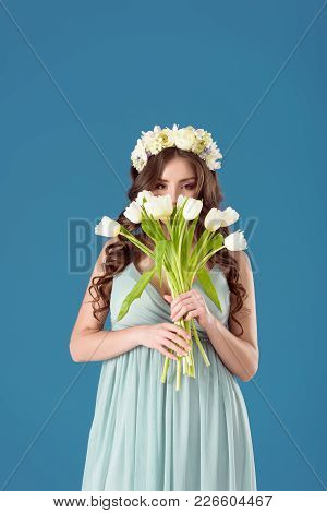 Beautiful Girl With Flowers Wreath On Head Sniffing Tulips Isolated On Blue
