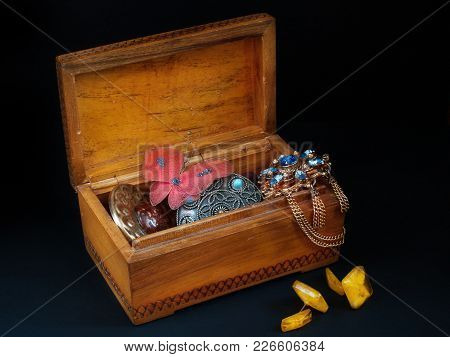 An Open Old Wooden Casket With Old Broken Decorations Inside And Amber Cuff Links Near The Casket St