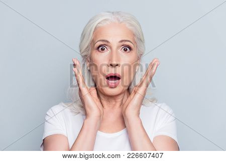 Pretty, Nice, Old, Shocked, Scared Woman With Wide Open Eyes And Mouth In T-shirt Holding Palms Near
