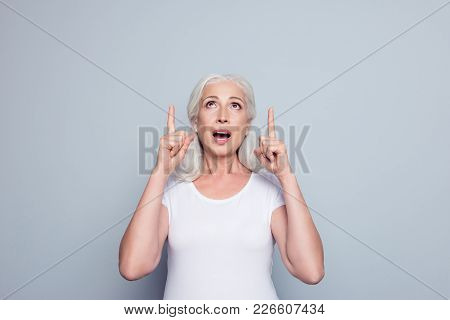 Portrait Of Perfect, Nice, Old, Impressed Woman In T-shirt Demonstrate, Looking, Pointing With Two F
