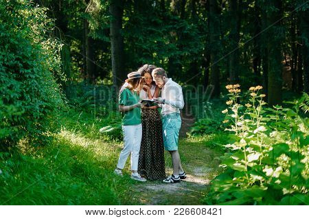 Three Beautiful Young Multi-ethnic Friends Are Discussing The Book In The Forest. Reading The Book I