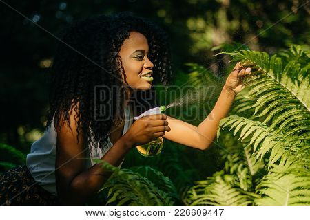 Side Outdoor Portrait Of The Attractive Young African Girl With Green Lipstick Is Using The Green Pl