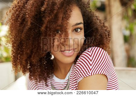Close Up Shot Of Lovely Dark Skinned Mixed Race Female With Wavy Dark Hair, Smiles Pleasantly, Wears