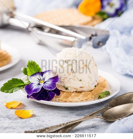 Vanilla Ice Cream Scoop With Edible Flowers Pansy. Summer Food Concept.