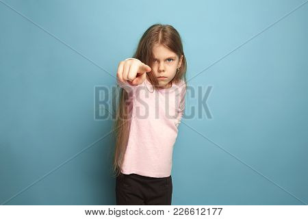 The Determination, Indictment And Choice. The Serious Teen Girl On A Blue Studio Background Pointing