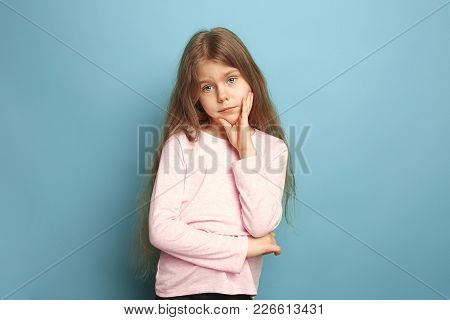 The Thoughtful Girl. The Sad Teen Girl On A Blue Studio Background. Facial Expressions And People Em