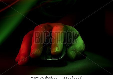 The Hand Lies On The Computer Mouse. Green And Red Light Effect. Gamer.