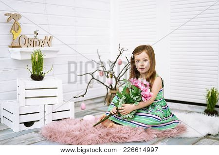 Four Years Old Girl Holding Pink Flowers In Her Hands On White Background Around Easter Decorations