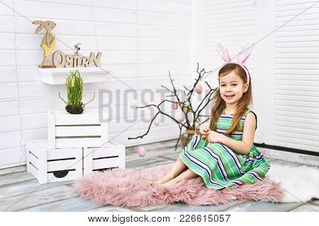 Four Years Old Smiling Girl Sitting On White Background Around Easter Decorations