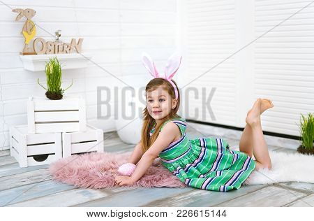 Four Years Old Girl With Bunny Ears And Big Egg In Her Hands On White Background Around Easter Decor