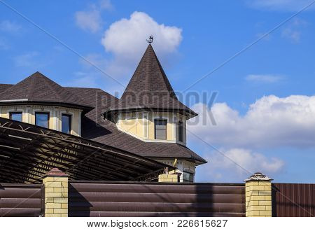 Decorative Metal On The Roof Of A Brick House. Fence Made Of Corrugated Metal
