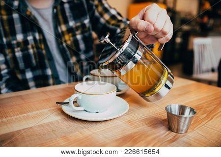 Man Fill Up Cup With Hot Tea From French Press
