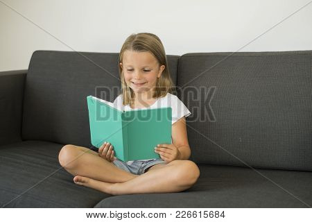 Young Sweet And Happy Little Girl 6 Or 7 Years Old Sitting On Home Living Room Sofa Couch Reading A