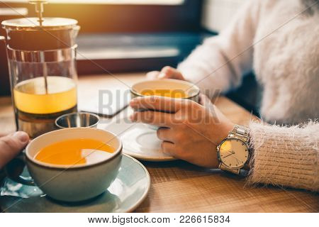 Woman Drink Hot Orange Tea In Cafe