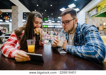 Young Couple Make Pause For Shopping Eat Burgers In Mall Cafe
